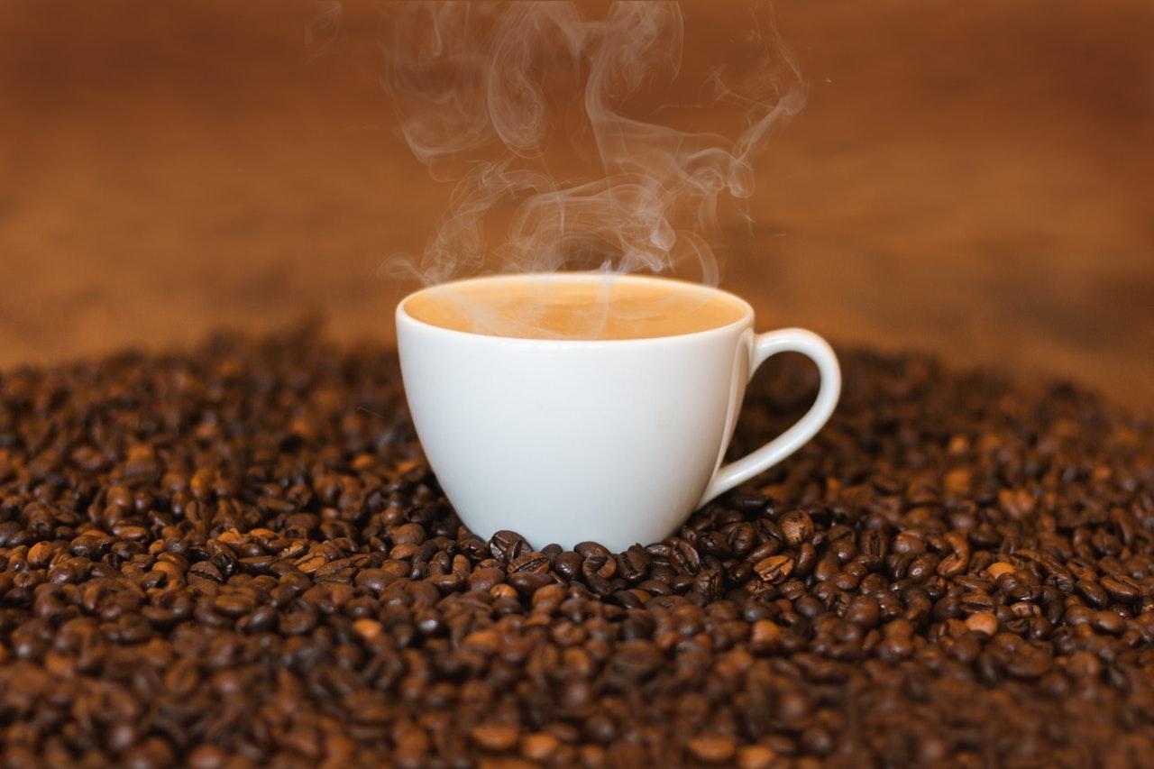 Vit kaffekopp placerad på kaffebönor