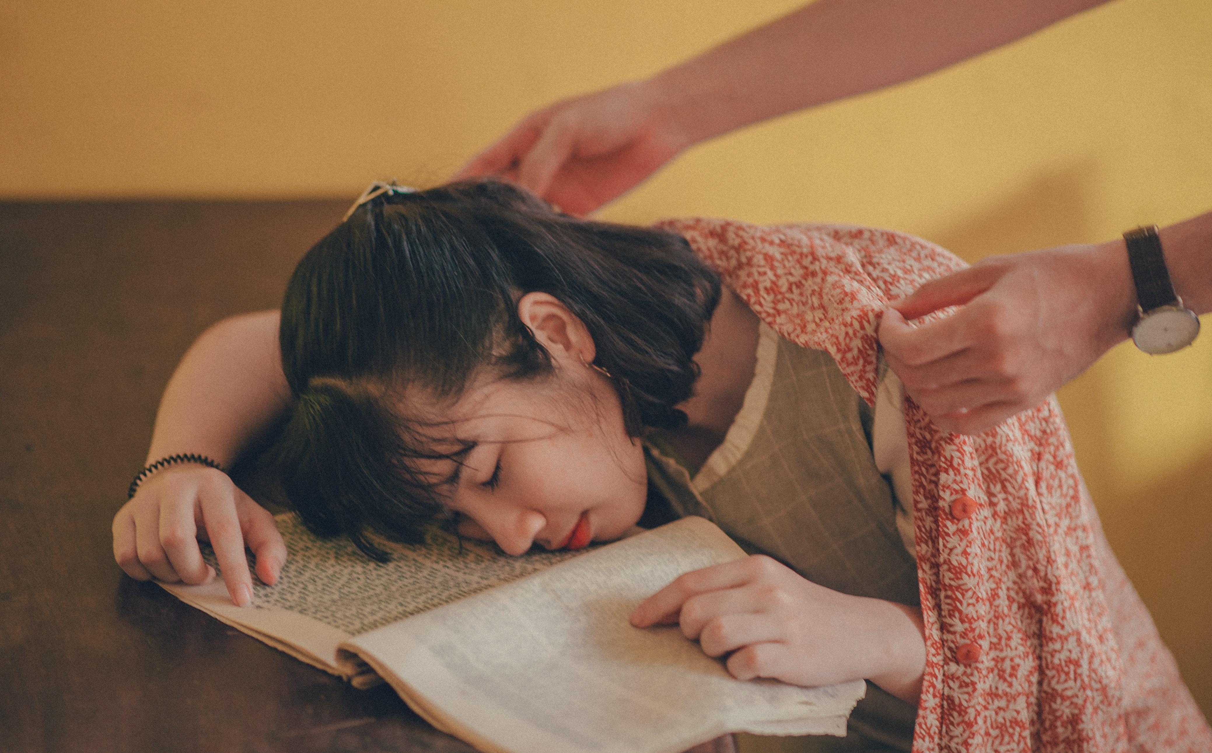 Flicka som somnat på bok
